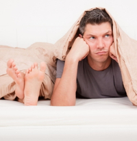 Angry man in bed with partner suffering from ed.