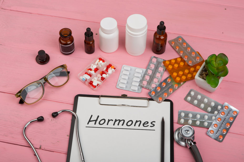 "Doctor workplace with clipboard and text ""Hormones"", medicine bottles, red stethoscope, eyeglasses and pills on pink wooden table. Medication prescription. Health care or illness"