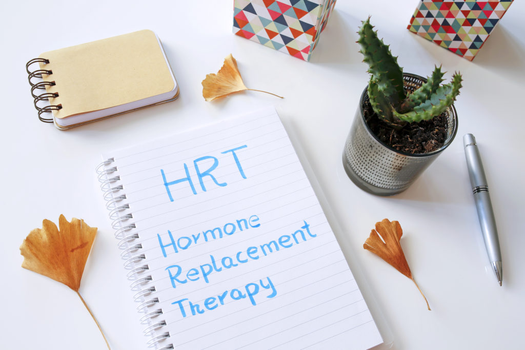 HRT Hormone Replacement Therapy written in notebook on white table